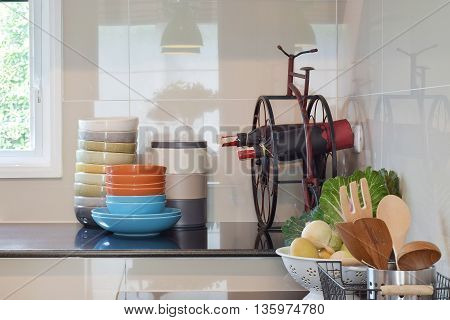 Colorful plates and bowls and wine bottles on black granite top in the kitchen