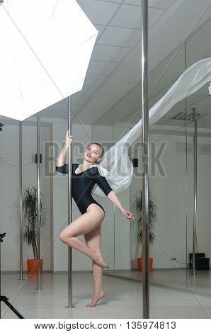 Girl Doing Exercises On The Pylon.