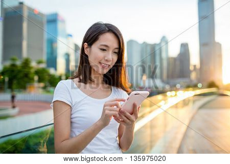 Asian woman use of mobile phone at sunset
