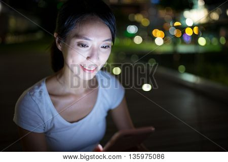 Woman looking at cellphone at night