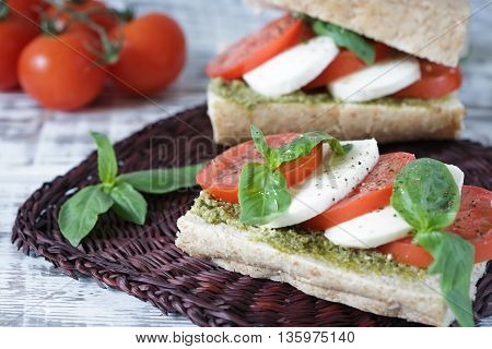 Closeup of a fresh sandwich with mozzarella tomatoes pesto and basil. Sandwich Caprese. Selective focus.