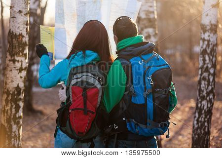 Man and woman tourists backpackers reading map on trip. Young couple hikers looking at map.