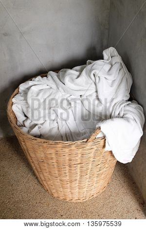 clothing basket and white towels at the corner of room