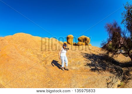 Nature reserve Spitzkoppe in Namibia. Picturesque stone arches are painted by iron oxides in orange color. Elderly woman - tourist with a camera down the steep mountainside
