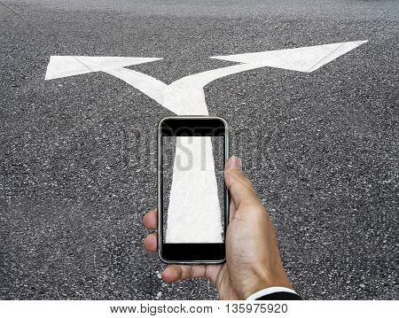 Mobile phone on hand with arrows road leading sign symbol, concept of choice about way of life, business and etc.