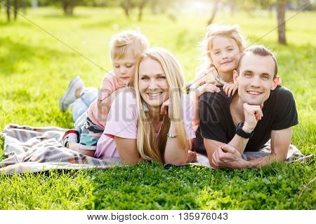 Family playing in the park on the grass. lens flare effect