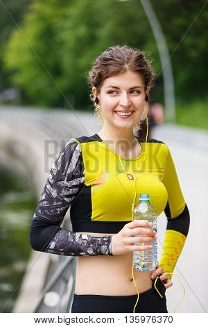 Young athletic woman in yellow tracksuit with water
