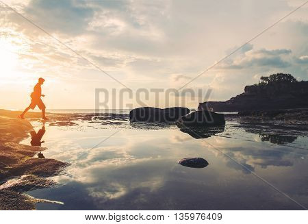 Silhouette, a guy walking with reflection on the island in sunset, vintage tone, soft focus