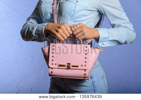 trendy woman in jeans and denim shirt with pink handbag in hands beige background