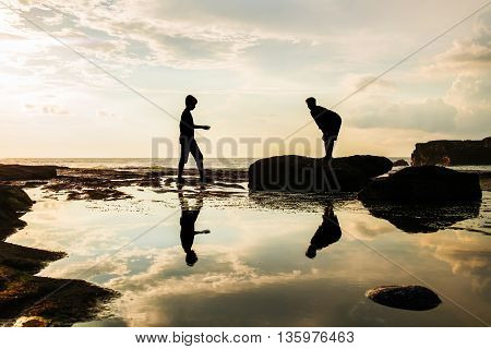 Silhouette, two man with shadow reflection on water in the island at sunset