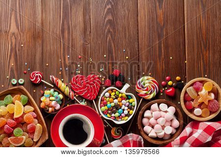 Coffee, colorful candies, jelly and marmalade on wooden background. Top view with copy space