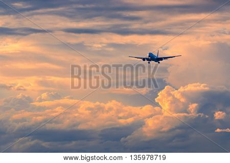 Commercial passenger airplane coming in for landing against beautiful colorful sunset color and contrast enhanced