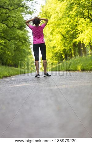 Beautiful mixed race African American young woman girl teenager fitness running jogging resting on road lined with spring or summer green trees