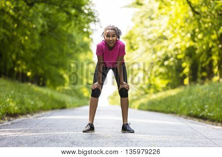 Beautiful mixed race African American young woman girl teenager fitness running jogging on a rad lined with green trees in spring or summer