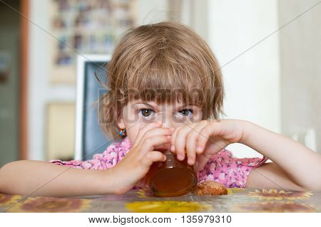 little girl sits at table and drinks tea from a transparent glass