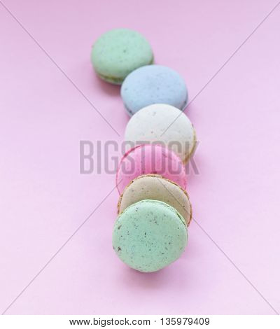 French multicolored almond cookies macaroons on a pink background