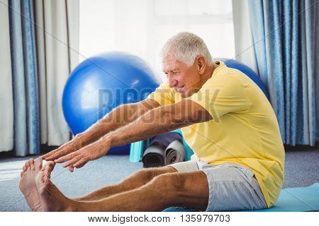 Side view of senior stretching arms in studio