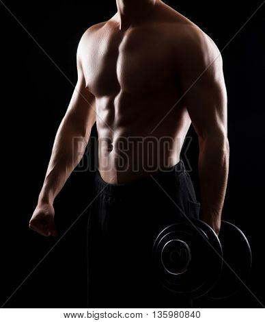Strong, fit and sporty bodybuilder man with a dumbbell over black background.