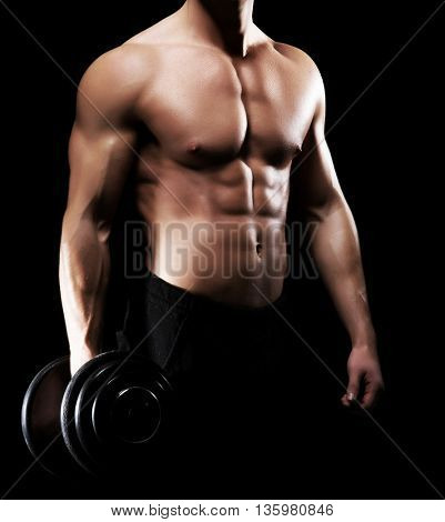 Strong, fit and sporty bodybuilder man having a workout with dumbbell on bicep over black background.