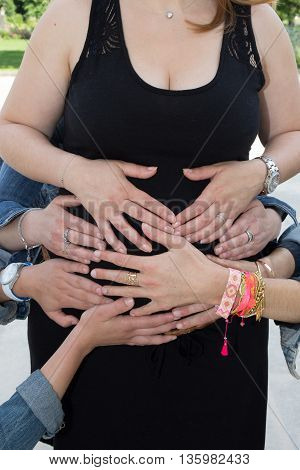 Plenty Of Hands Of People On Belly Of A Pregnant Woman
