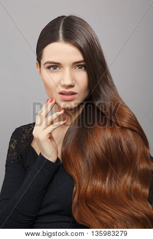 Portrait of beautiful model woman demonstrating her gorgeous and luxurious brown hair. Female with modern hairstyle posing over grey background in studio.