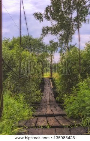 Wooden suspension bridge over the river in the forest