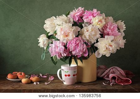 Still life with a bouquet of peonies in a jug and peaches on a green background.