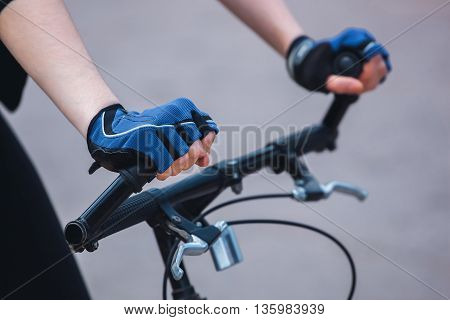 Hands of a girl in a sports blue-black gloves holding on to the steering wheel of the bicycle. Close-up.