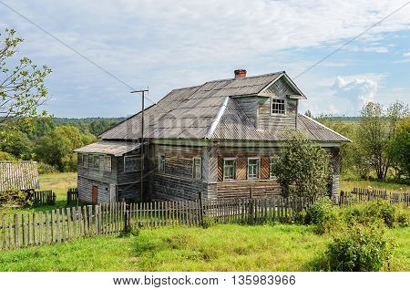 Big country wooden house with mansard in russian village