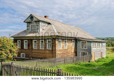 Beautiful country wooden house with mansard Russia. Summer sunny day