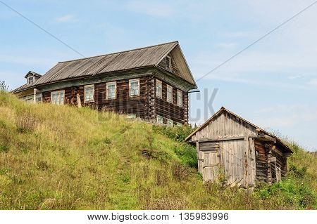 Old big log house and a shed in russian village Vologda region. Summer day