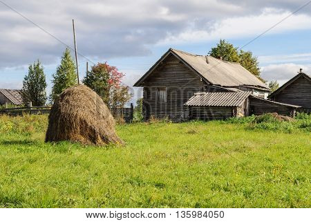 Rural landscape with old log house and haystack in the vegetable garden Vologda region Russia