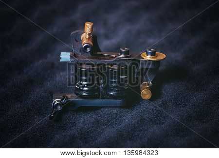 Some tattoo machine - frame with coils lying on a black textured foam rubber.
