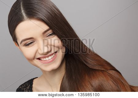 Portrait of happy smiling young woman posing with long brown hair over grey background. Fashion and vogue concepts. Modern hairstyle in studio.