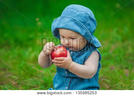 Little girl in blue jeans and a hat on his head in a blue dress sitting on a sunny day in the park on the grass smiling and holding a red juicy apple.