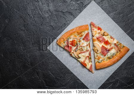 Cut into slices delicious fresh pizza with mushrooms and ham on a dark background. Top view . Pizza on the black table.