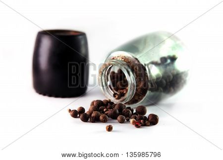Different kinds of peppercorns scattered on a white background of hand-mill for pepper
