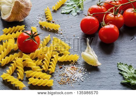 Pasta ingredients (fusilli) on black slate background. Fresh tomatoes garlic parsley salt and pepper.