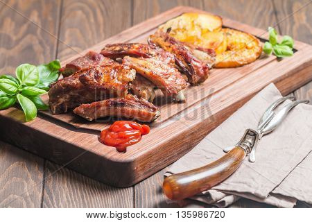 elicious Grilled Pork Rib and Fried Potato Wedges with Sauce on wooden cutting board
