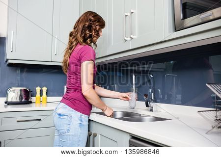 Side view of woman filling water in glass from faucet at kitchen sink