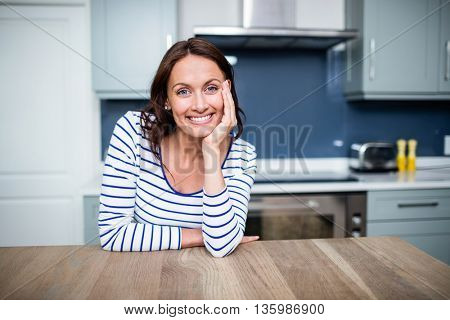 Portrait of cheerful young woman sitting at table in kitchen
