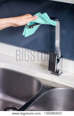 Cropped image of woman wiping faucet by sink at kitchen counter
