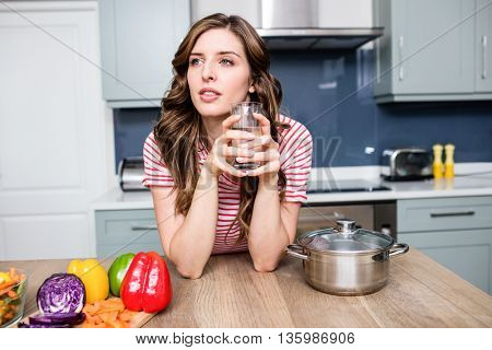 Thoughtful young woman holding drinking glass at table in house