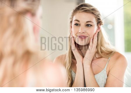 Happy young woman looking in mirror at home