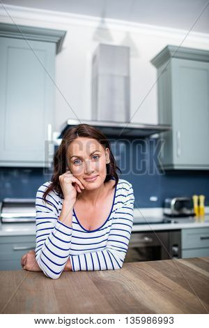 Portrait of smiling young woman sitting at table in kitchen