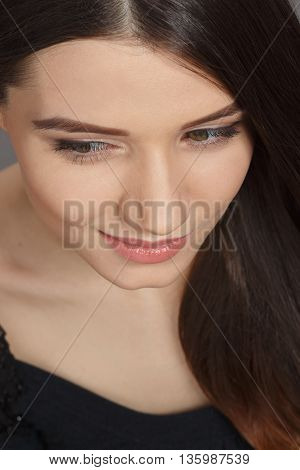 Closeup portrait of pretty smiling woman with long brown hair. Young lady demonstrating her modern hairstyle in studio.