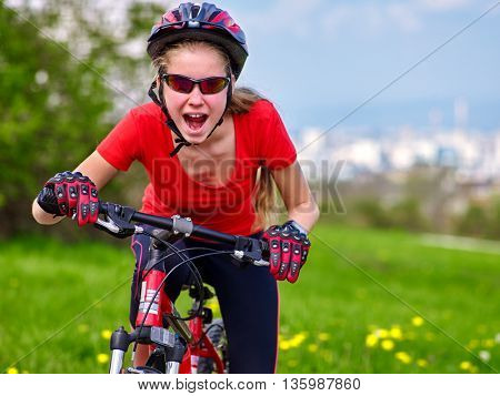 Bikes cycling girl. Girl rides bicycle out city. Girl in cycling. Cycling is good for health. Cyclist is looking at city in distance. Background city.