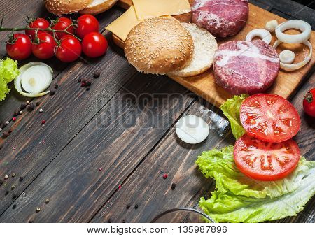 Ingredients for making homemade burger on wooden cutting board.