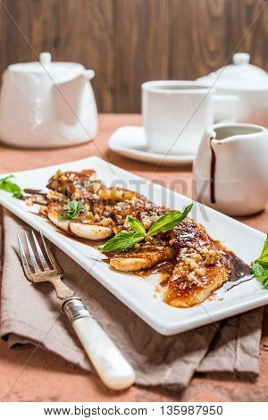 Grilled banana with walnut and chocolate sauce  on white plate over brown background