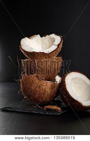 Stack of coconut shells on dark background